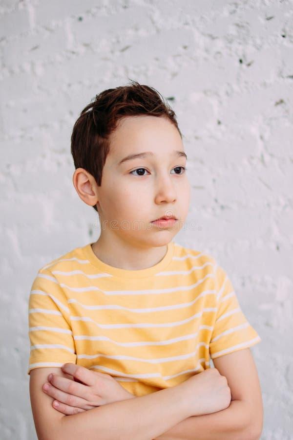 Garçon triste indifférent de tween mignon dans le T-shirt jaune faisant le baiser à la main d'isolement sur le fond blanc de mur photo stock
