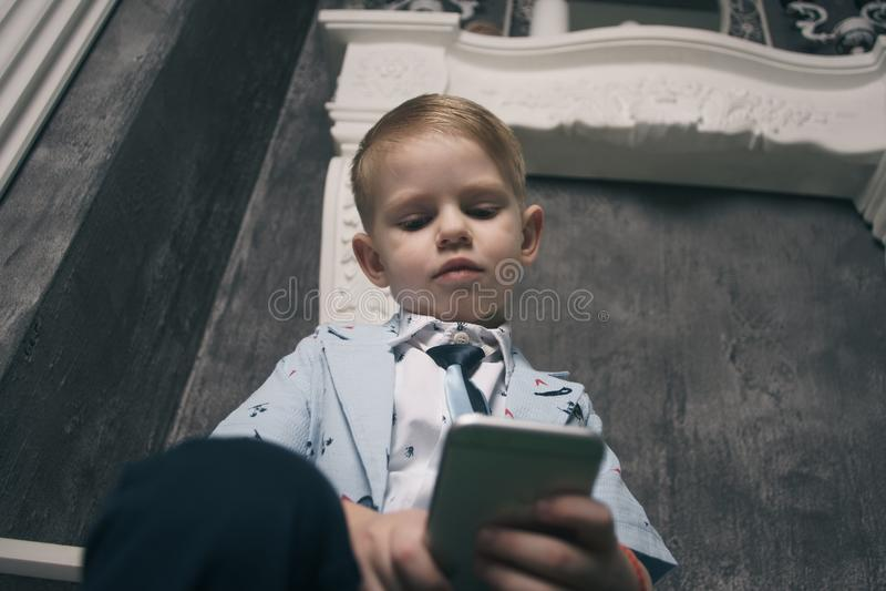 Garçon triste regardant le téléphone portable avec photos stock