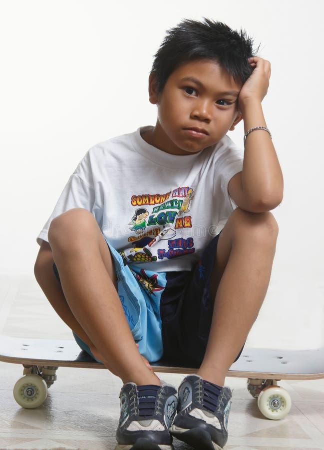 Garçon triste s'asseyant sur sa planche à roulettes photo stock