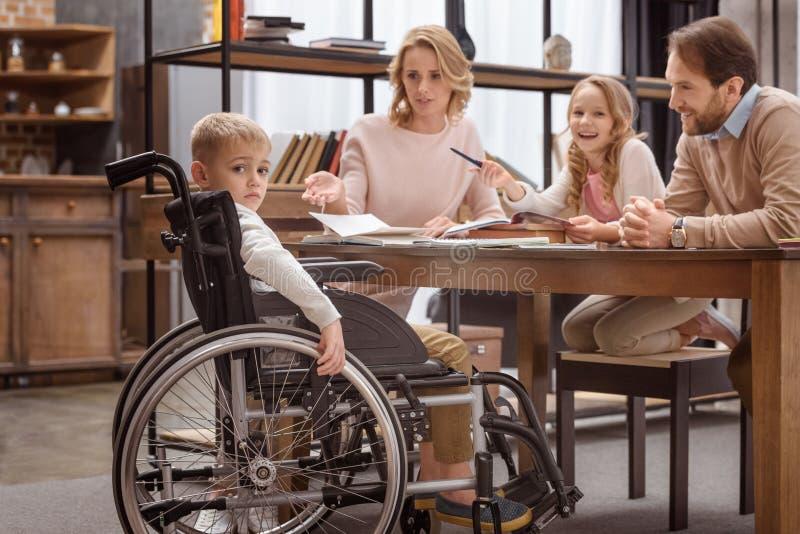 garçon triste sur le fauteuil roulant regardant la caméra et son image stock