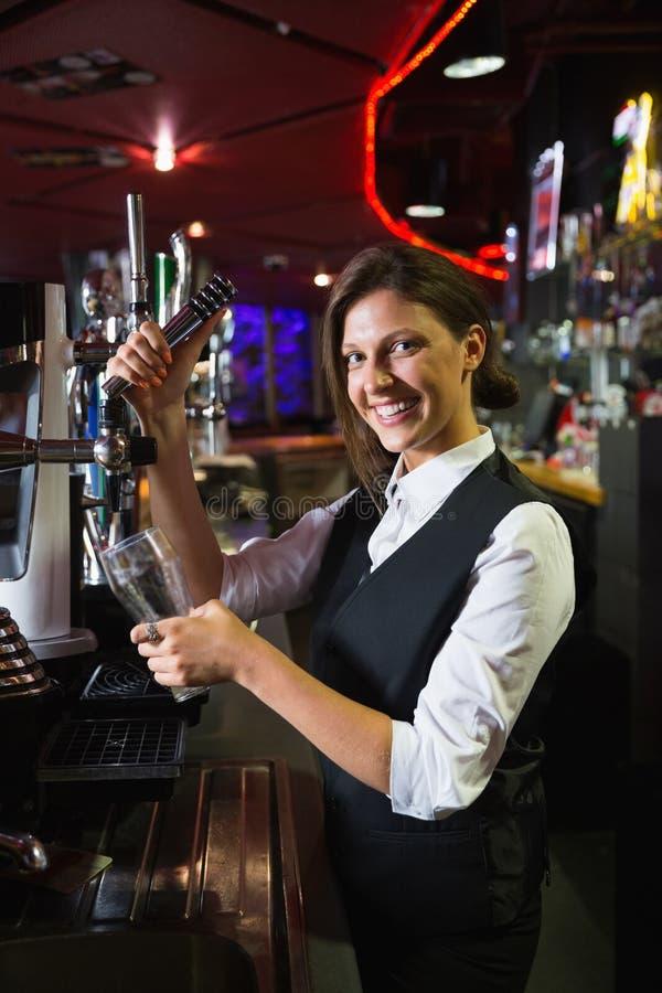 Garçonete feliz que puxa uma pinta da cerveja imagens de stock royalty free