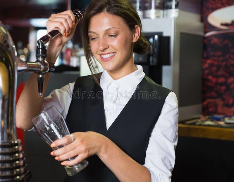 Garçonete feliz que puxa uma pinta da cerveja fotografia de stock royalty free