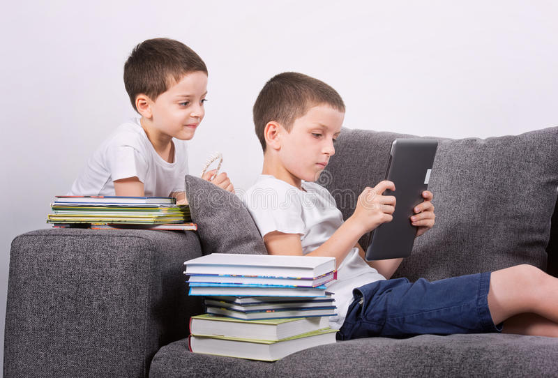 Garçons à l'aide d'une tablette sur le sofa images stock