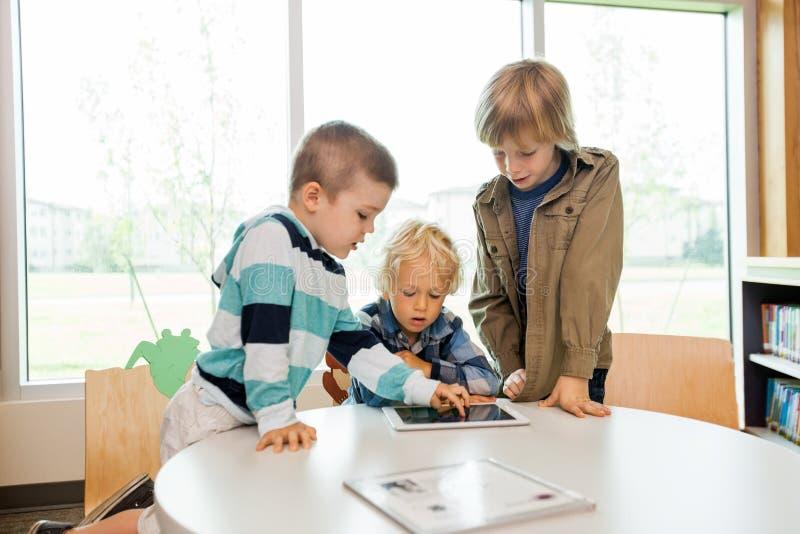 Garçons à l'aide de la Tablette de Digital dans la bibliothèque photo stock
