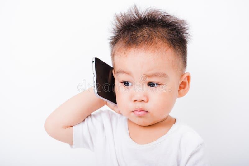 Garçons asiatiques d'enfant de portrait 1 an 6 mois appelant avec le smartphon photographie stock libre de droits