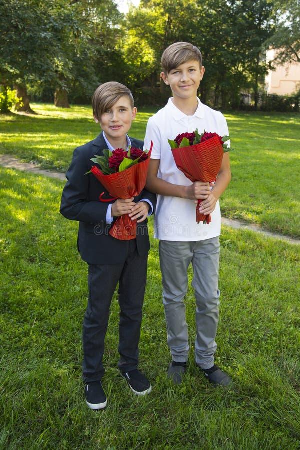 Garçons avec des bouquets des roses au jour du ` s de mère photos stock