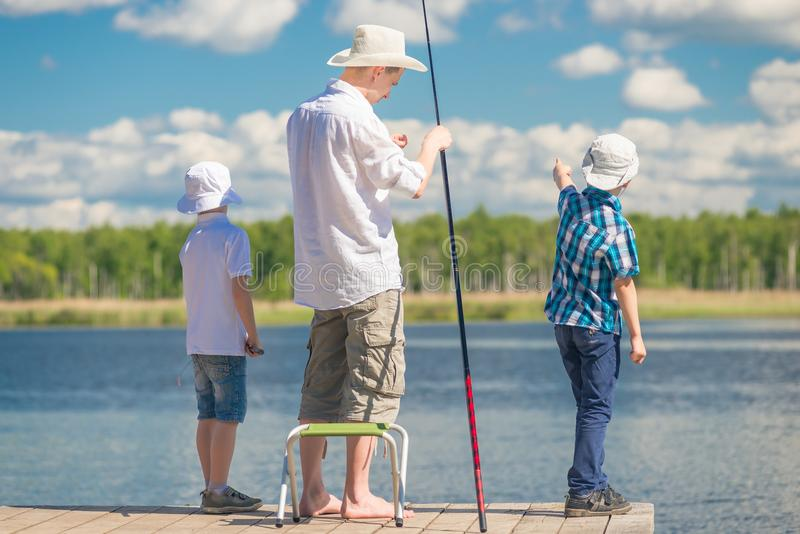 garçons avec le père sur la pêche dans un bel endroit photographie stock