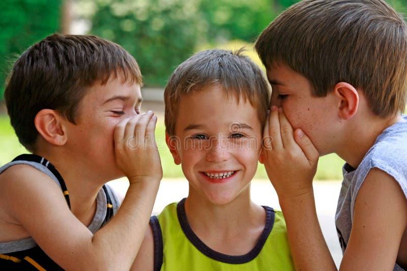 Garçons disant des secrets photo stock