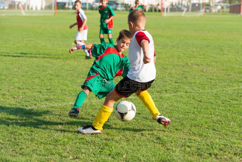 Garçons donnant un coup de pied le football photographie stock