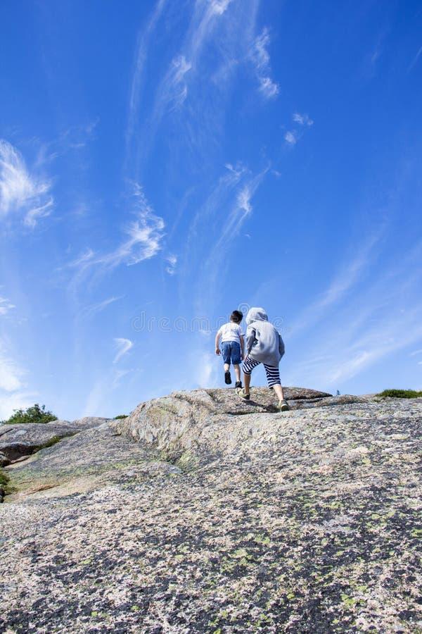 Garçons escaladant une montagne photographie stock