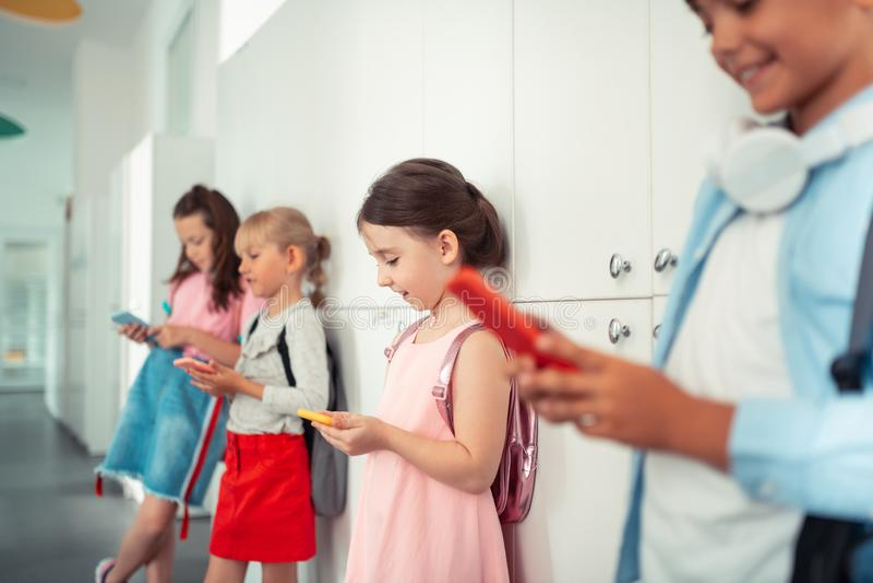 Garçons et filles adonnés aux instruments jouant des jeux aux téléphones images stock