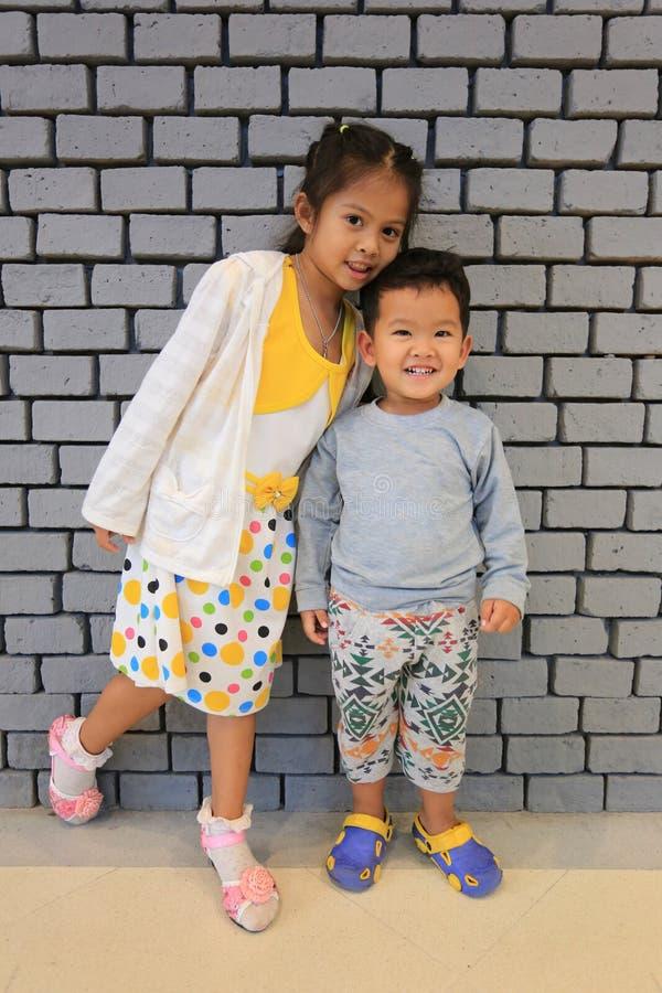 Garçons et filles asiatiques dans le sourire sur le fond de mur de briques image stock