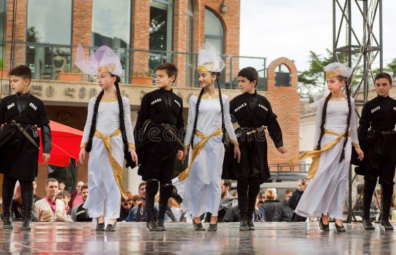 Garçons et filles dansant dans des costumes traditionnels pendant la représentation en Géorgie photos libres de droits