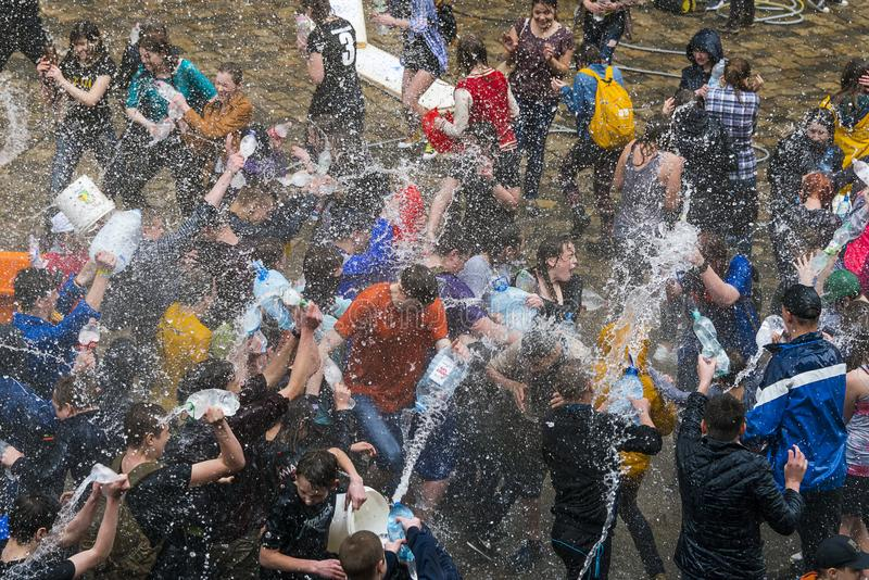 Garçons et filles heureux versant l'eau sur l'un l'autre photo stock