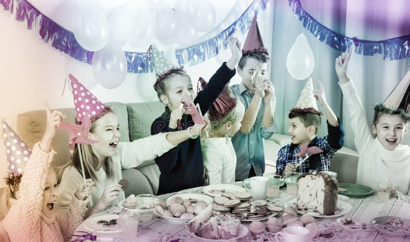 Garçons et filles se comportant en plaisantant pendant la pièce d'anniversaire de friend's photographie stock