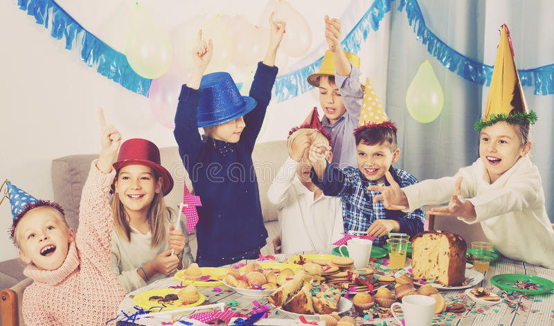 Garçons et filles se comportant en plaisantant pendant la pièce d'anniversaire de friend's photo libre de droits
