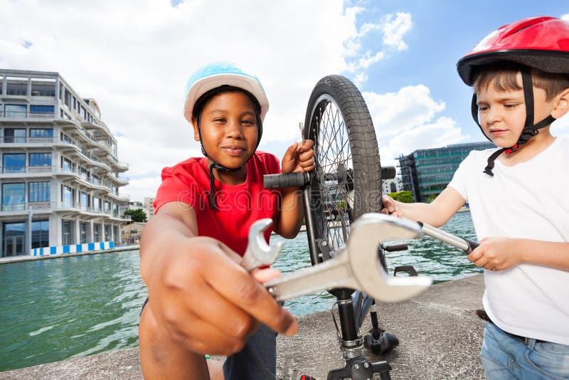 Garçons heureux fixant le vélo ensemble dehors en été image libre de droits