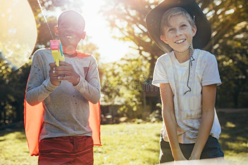 Garçons heureux jouant des armes à feu d'eau dehors photographie stock libre de droits