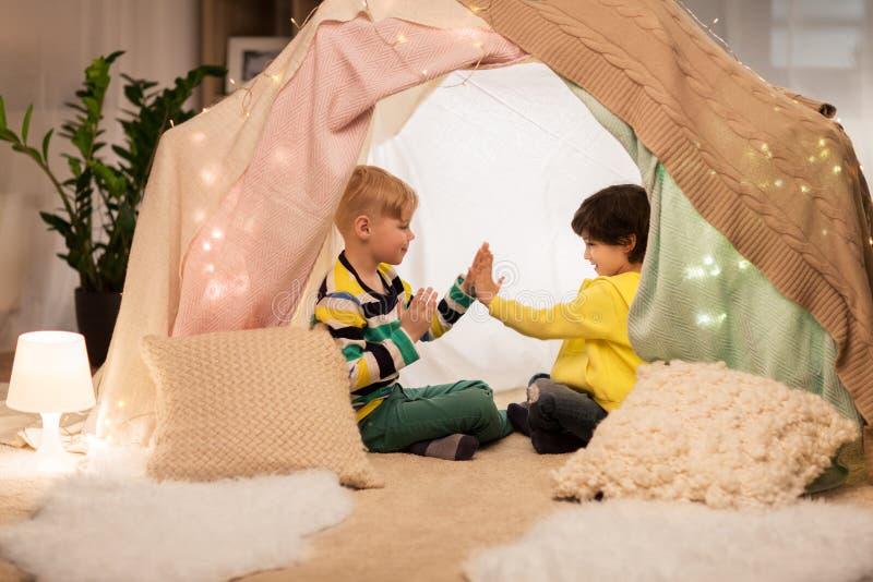 Garçons jouant le jeu de applaudissement dans la tente d'enfants à la maison photographie stock libre de droits