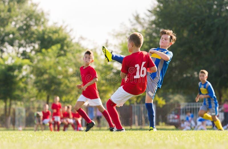 Garçons jouant le jeu de football du football sur le champ de sports photos libres de droits