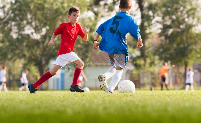 Garçons jouant le jeu de football du football sur le champ de sports image stock