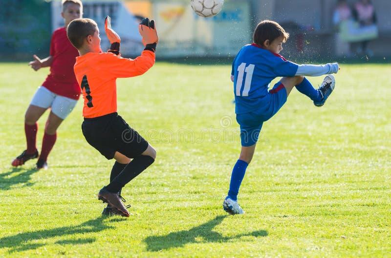Garçons jouant le jeu de football du football sur le champ de sports photo stock