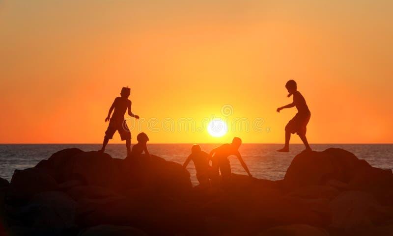 Garçons jouant sur la plage image stock