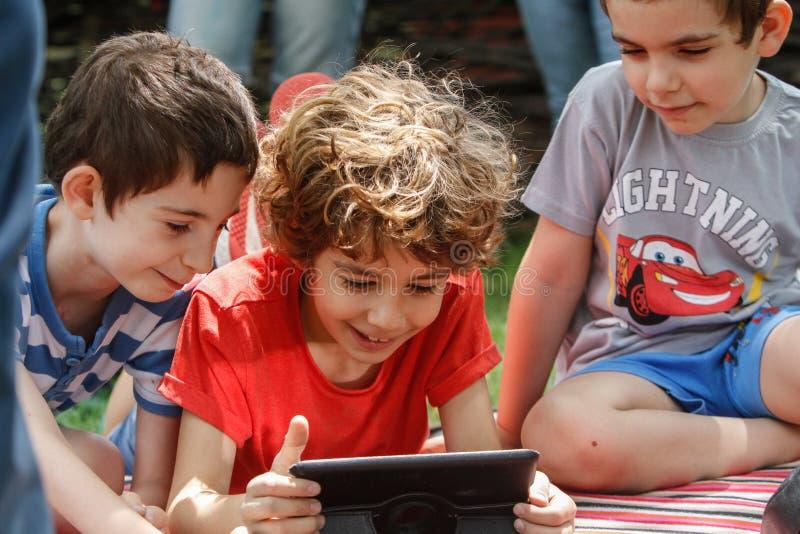 Garçons jouant sur un comprimé photographie stock libre de droits