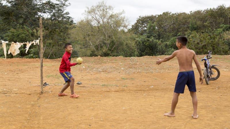 Garçons laotiens jouant la boule dans le wanrong, Laos image libre de droits