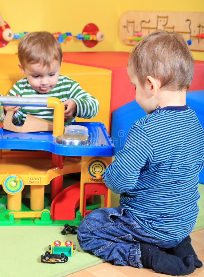 Garçons mignons jouant dans le jardin d'enfants photos stock