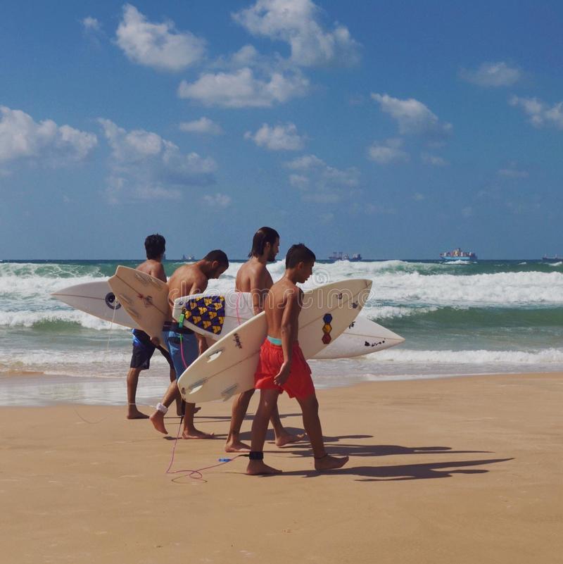 Garçons non identifiés marchant avec des panneaux de ressac sur la plage photo stock