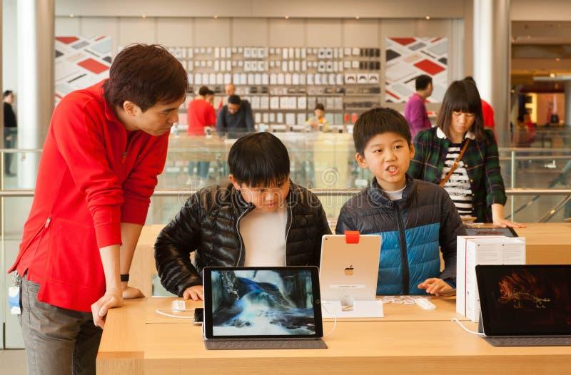 Garçons non identifiés parlant des dispositifs à l'intérieur d'iStore avec iPod et instruments photos stock