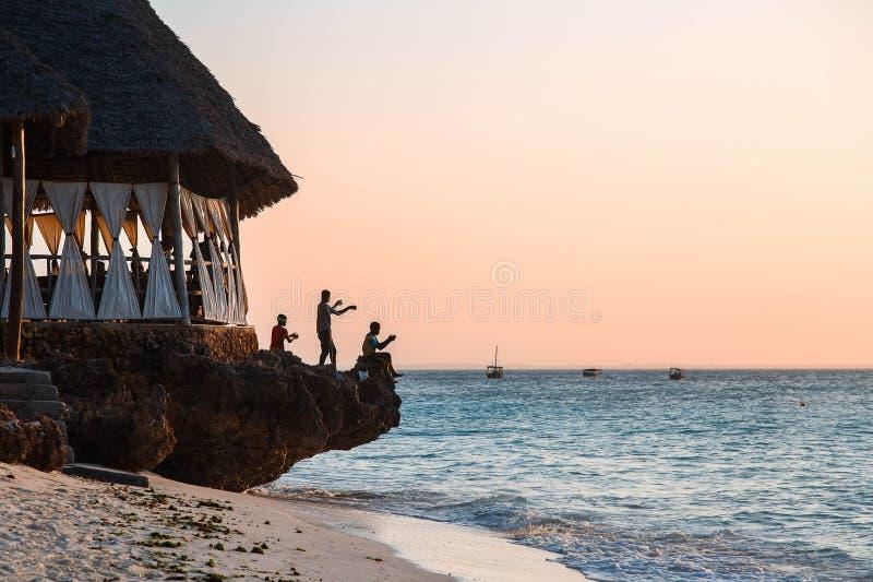 Garçons pêchant au coucher du soleil sur la roche sur l'océan, Nungwi, Kendwa, île de Zanzibar, Tanzanie image stock