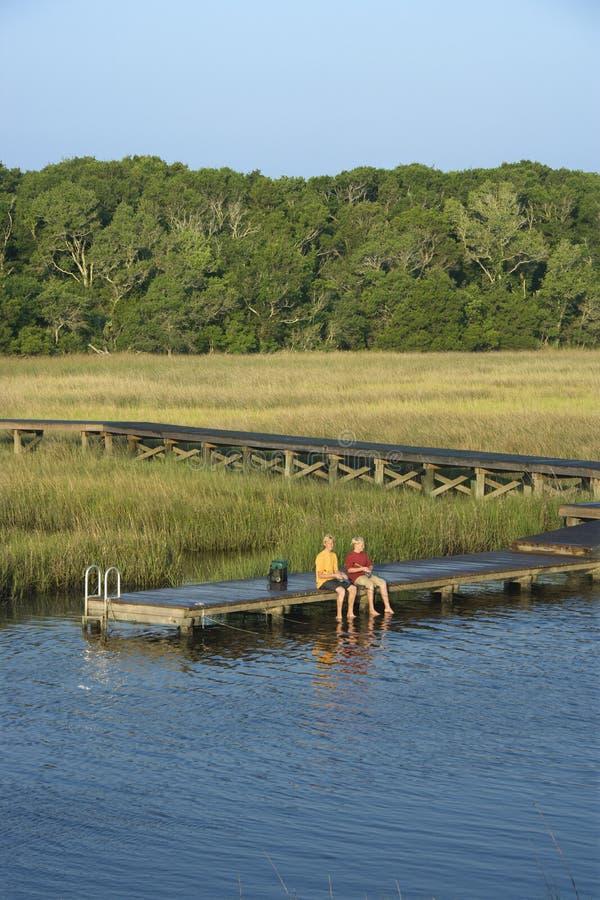 Garçons pêchant sur le dock. image stock