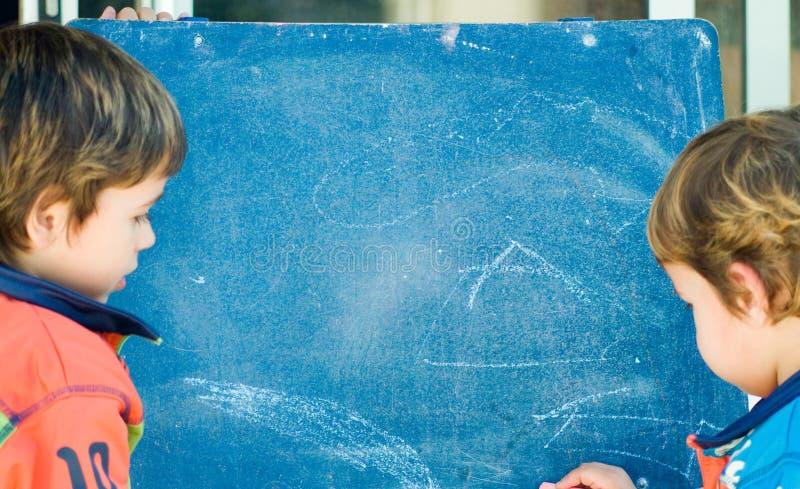 Garçons peignant sur un tableau noir photographie stock libre de droits