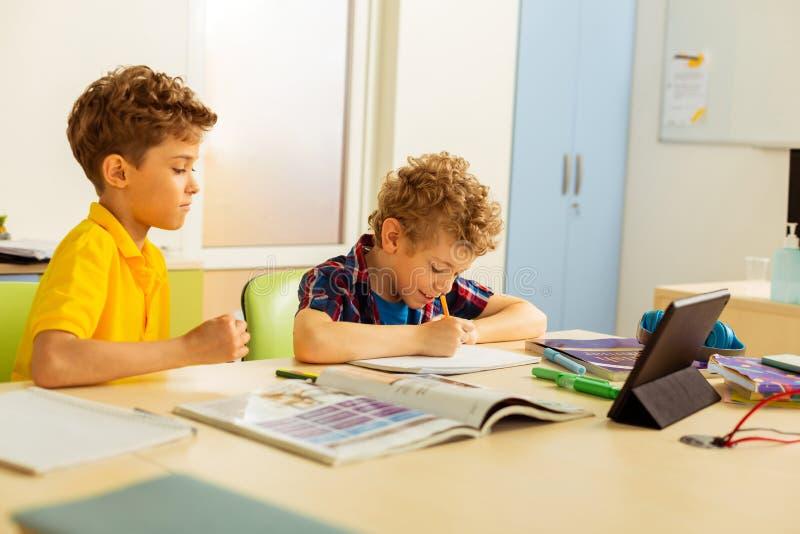 Garçons positifs joyeux appréciant leur leçon d'école image libre de droits