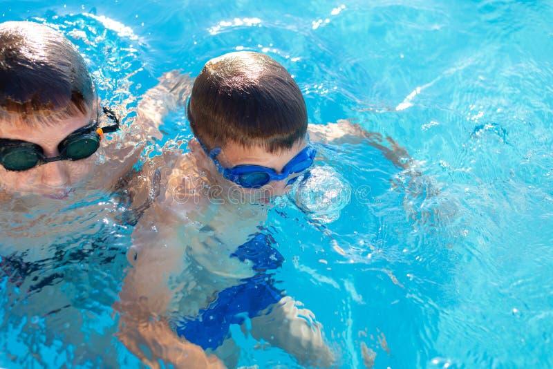 Garçons retenant le souffle sous l'eau dans la piscine photos libres de droits