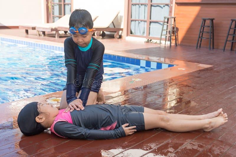 Gar?on aidant noyant la fille d'enfant dans la piscine en faisant le CPR image libre de droits