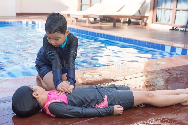 Gar?on aidant noyant la fille d'enfant dans la piscine en faisant le CPR photos stock