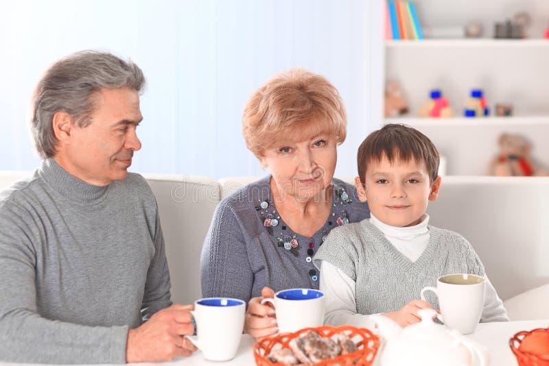 Gar?on buvant le chocolat chaud et les grands-parents heureux photo libre de droits