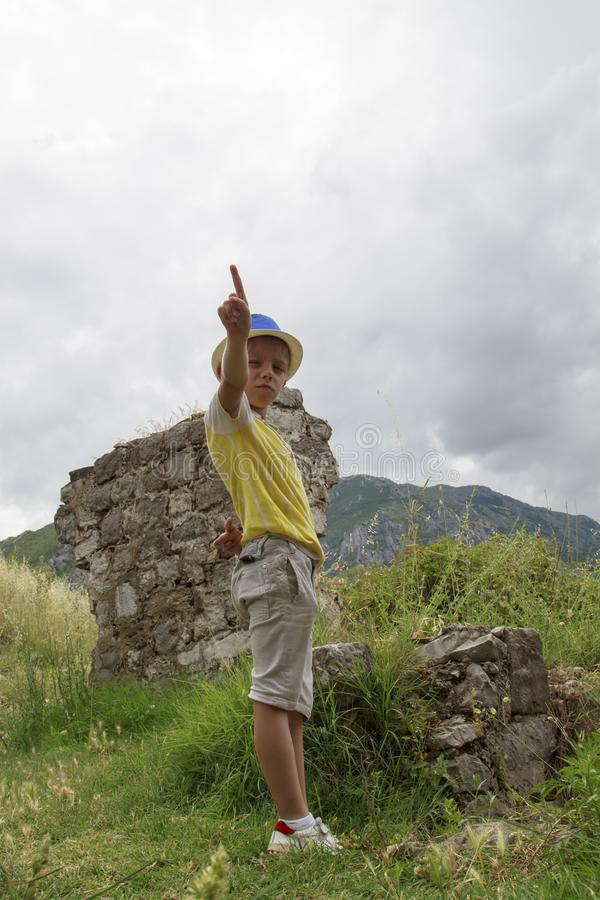 gar?on dans un chapeau bleu staing pr?s des ruines de la forteresse antique de S images stock