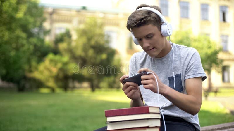 Gar?on de l'adolescence dans des ?couteurs jouant le jeu mobile au lieu du travail, temporisation photos libres de droits
