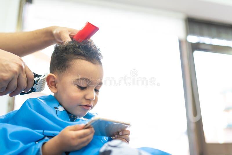 Gar?on mignon obtenant une coupe de cheveux dans Barber Shop Concept de beaut? photo stock