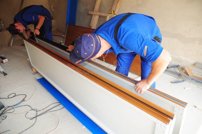 Garażu drzwi naprawa Kontrahent instaluje garażu garażu drzwiową weatherproofing drzwiową fokę Zamienia garaż drzwiowych fok doln zdjęcie royalty free