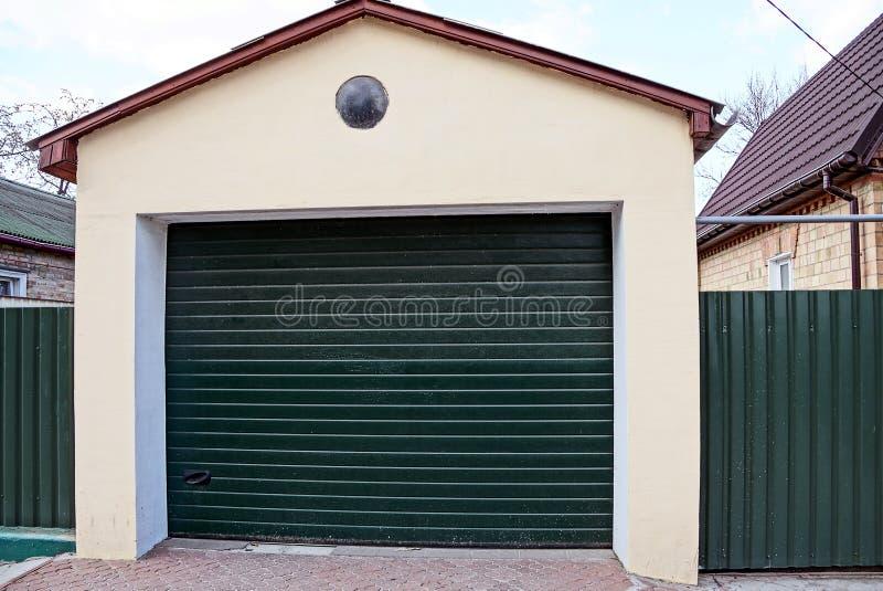 Garage con i portoni verdi chiusi e la parte del recintare la via vicino alla strada immagini stock libere da diritti
