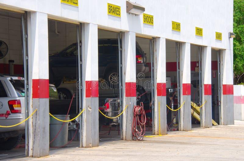 Garage de réparation automatique avec des véhicules sur des ascenseurs photo libre de droits