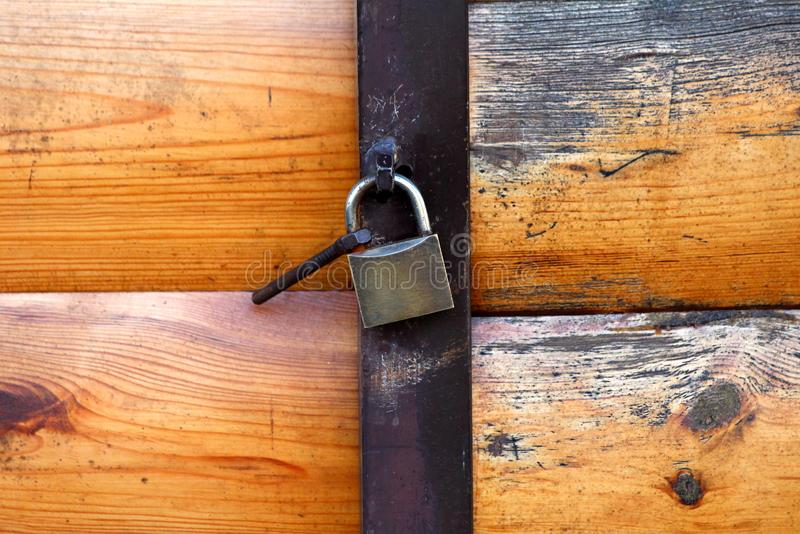 Garage doors made of wooden boards with interesting texture closed with metal hinge and locked with strong padlock. On warm sunny spring day royalty free stock photo