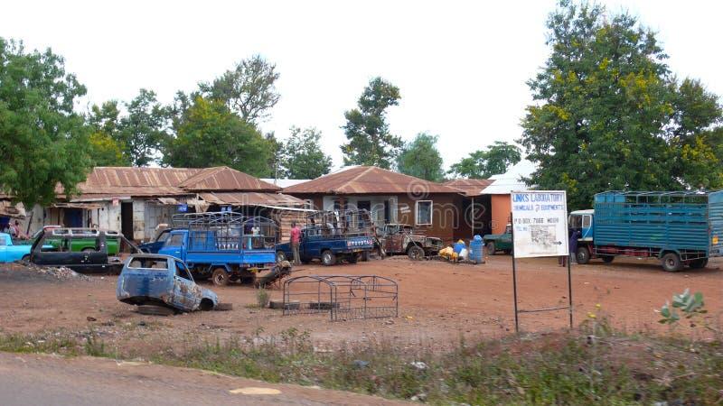 Garage en materiaal de levering slaat in landelijk Tanzania met beschadigde en oude voertuigen in de binnenplaats op royalty-vrije stock foto's