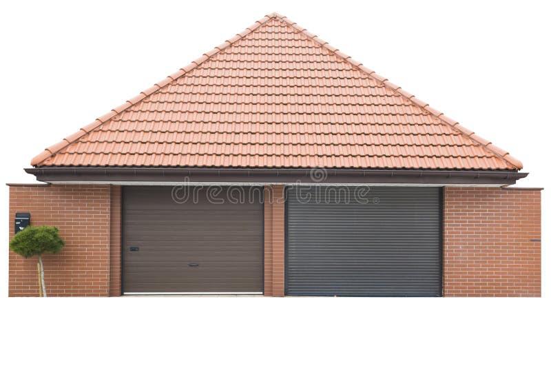 Garage för två bilar av röd tegelsten, taket av röda tegelplattor Trädet växer framme av garaget bakgrund isolerad white arkivfoto