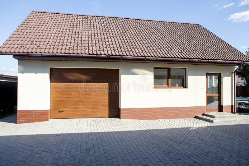 Garage garden house. Sliding gates. Hot sunny day. stock photos